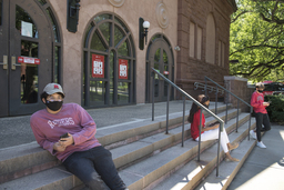 Three students sitting on steps with masks on.